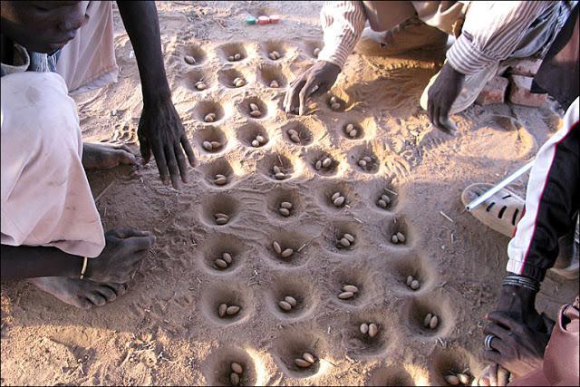 Una partita a Mancala giocata nella sabbia del Sudan (nel teso i credit)