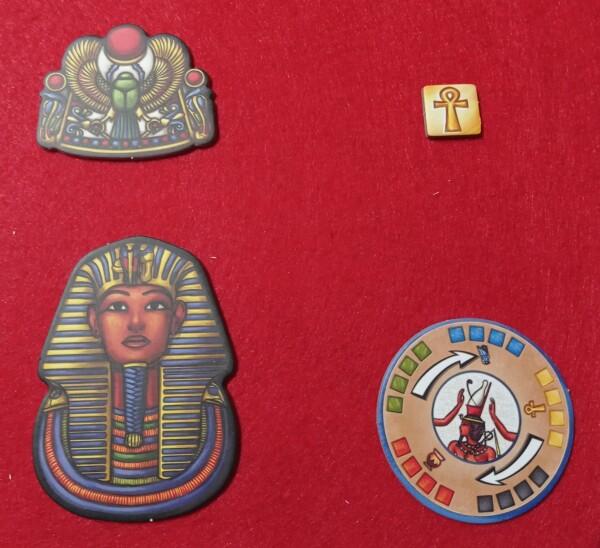 Altri segnalini, fra cui l'investitura a Faraone, il primo giocatore e la rotella che indica in che senso gira la ruota al centro del tabellone